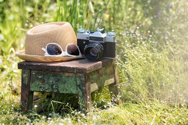여름 정원의 나무 의자에 있는 밀짚 모자 선글라스와 빈티지 카메라