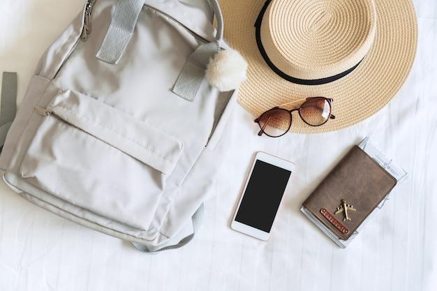 モダンなホテルの部屋のベッドで女性旅行者の麦わら帽子、サングラス、バッグ、パスポート、スマートフォン。旅行、リラクゼーション、旅、旅行、休暇のコンセプト。上面図とコピースペース。
