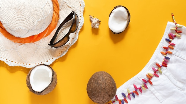 Straw hat, sunglasses, coconut halves a seashell and white shorts on yellow background