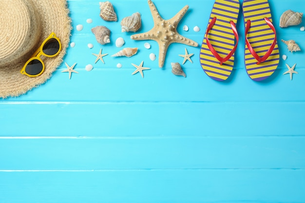 Straw hat, sunglasses, flip flops and many starfishes on color wooden background, space for text and top view. summer vacation concept