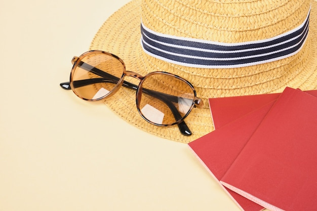 Straw hat, sunglasses and passports on beige background, travel and beach vacation concept