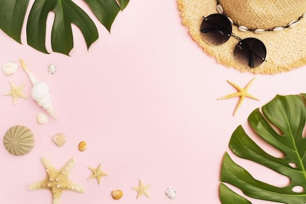 Солнцезащитные очки соломенной шляпы ракушки и листья монстеры на розовом фоне с копией пространства