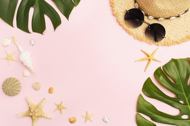 Straw hat sunglasses seashells and monstera leaves on a pink background with copy space