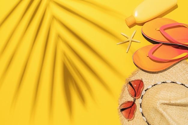Солнцезащитные очки в соломенной шляпе, тапочки и крем для загара на желтом фоне с тенью пальмовых листьев с копией пространства