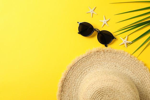 麦わら帽子、サングラス、ヒトデ、ヤシの葉のテキストとトップビューの色背景スペース。夏休みのコンセプト