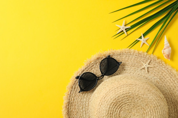 Straw hat, sunglasses, starfishes and palm leaf on color background space for text and top view. summer vacation concept