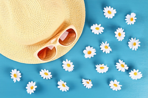 Straw hat and sunglasses with camomile on a blue background. top view. summer background. flat lay.
