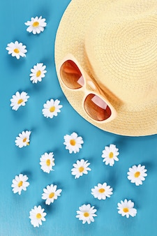 Straw hat and sunglasses with camomile on a blue background.