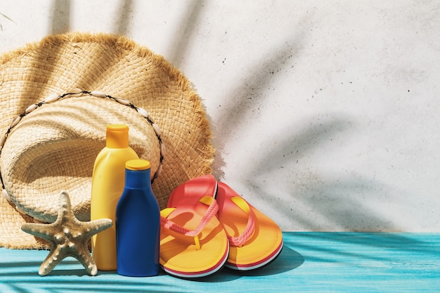 Straw hat sunscreen beach slippers and starfish on the table summer background