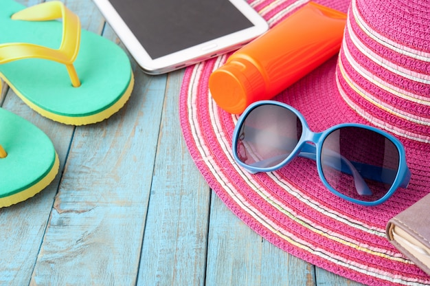 Straw hat tablet and sunglasses on blue wood.