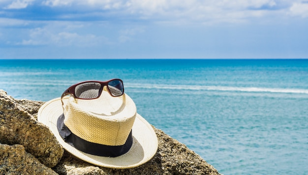 Straw hat with black ribbon and sunglasses on the rocks near the beach blue sea