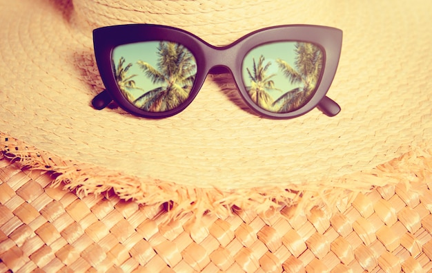 Straw hat with black trendy sunglasses with reflection of palms in them on a straw bag.