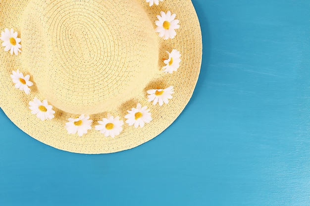Straw hat with camomile on a blue background. top view. summer background. flat lay.
