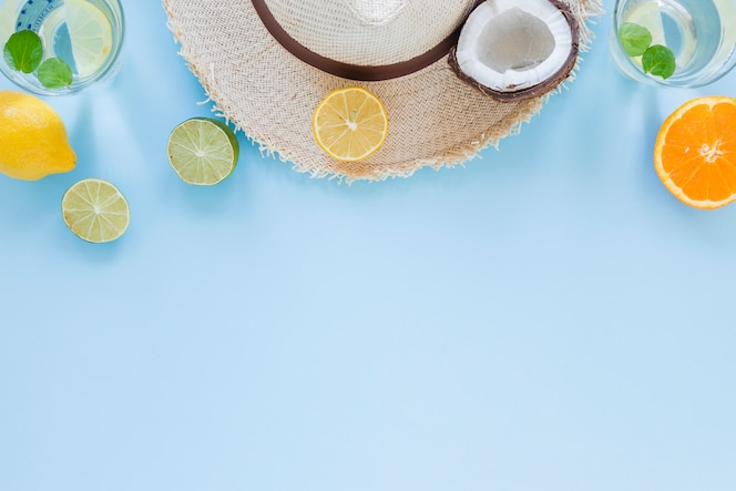 Straw hat with exotic fruits on table