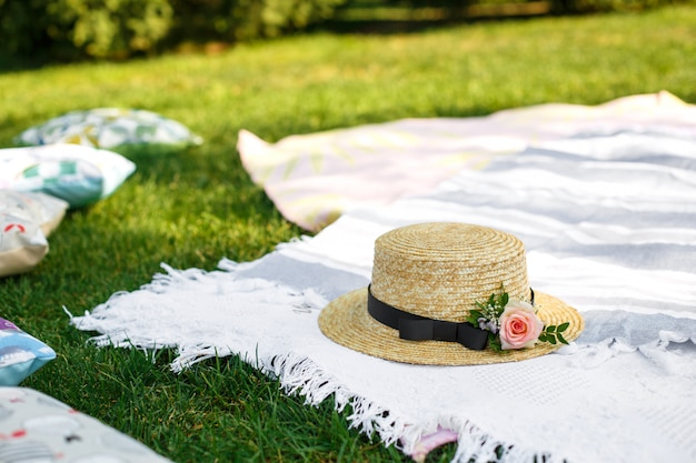 Straw hat with fresh flowers lay on a white picnic blanket at green lawn bright summer day background