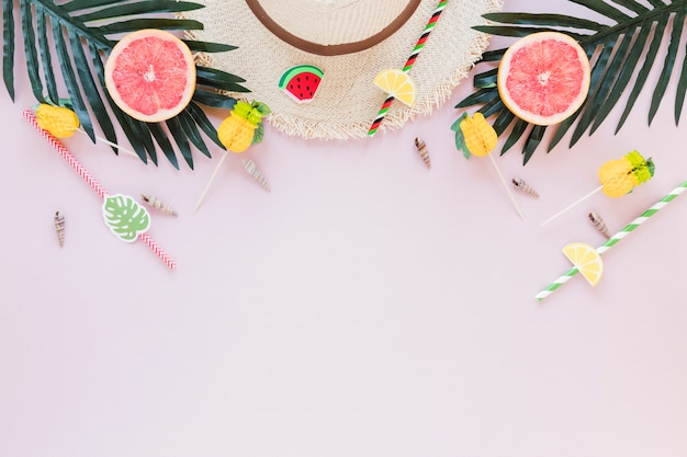 Straw hat with grapefruits and palm leaves