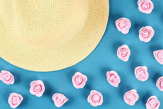 Straw hat with little roses on blue background. top view. summer background. flat lay.