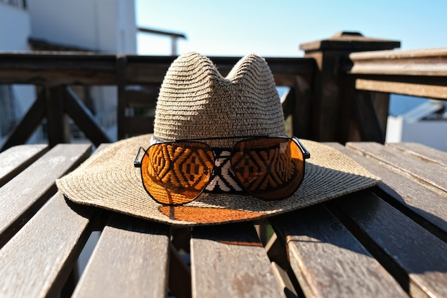 Straw hat with sun glasses on wooden terrace of holiday villa or hotel.