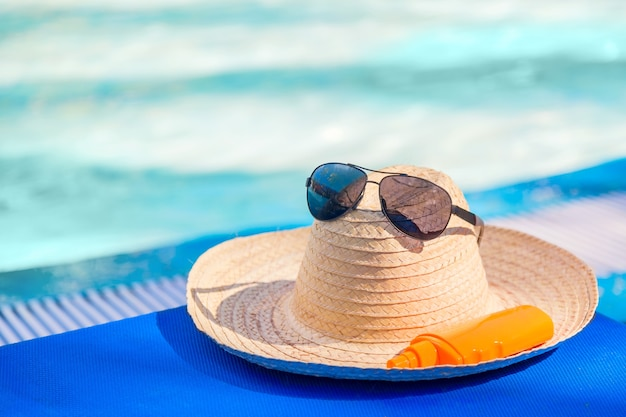 Straw hat with sunglasses and sunscreen lotion bottle near swimming pool