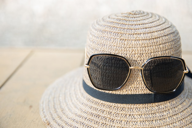 Straw hat with sunglasses on the wooden table in summer
