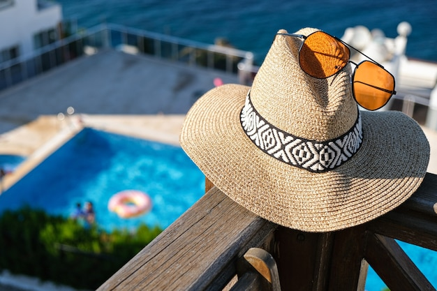 Соломенная шляпа с солнцезащитными очками деревянная терраса с видом на бассейн