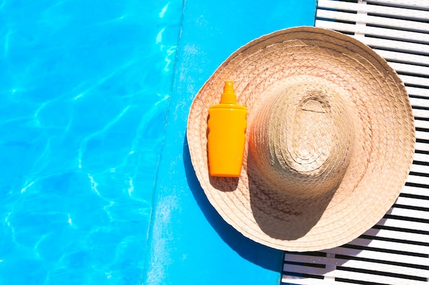 Straw hat with sunscreen lotion bottle near the surface of blue clear swimming pool