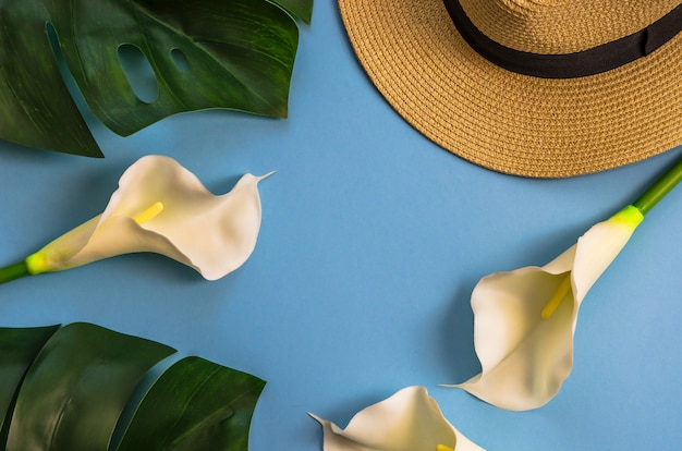 Straw hat with tropical leaves monstera and white callas, on light blue background