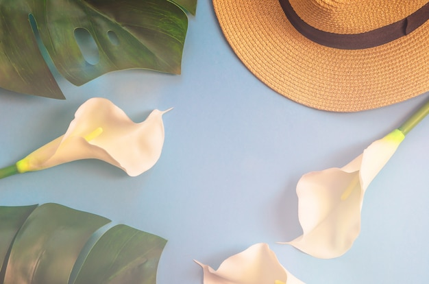 Straw hat with tropical leaves monstera and white callas, on light blue background.