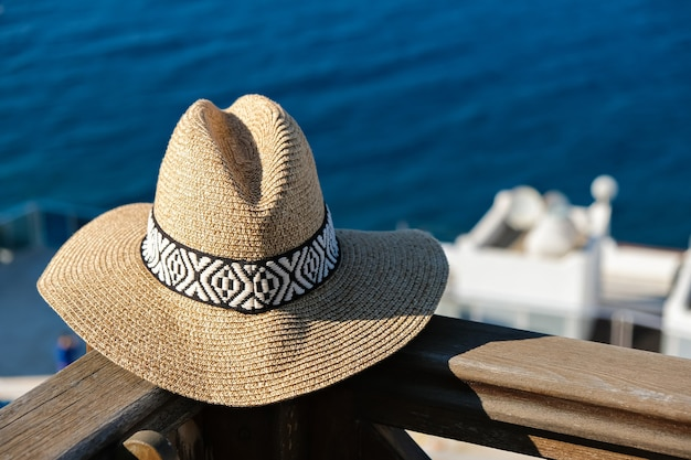 Straw hat with on wooden terrace of holiday villa or hotel with sea and wimming pool view