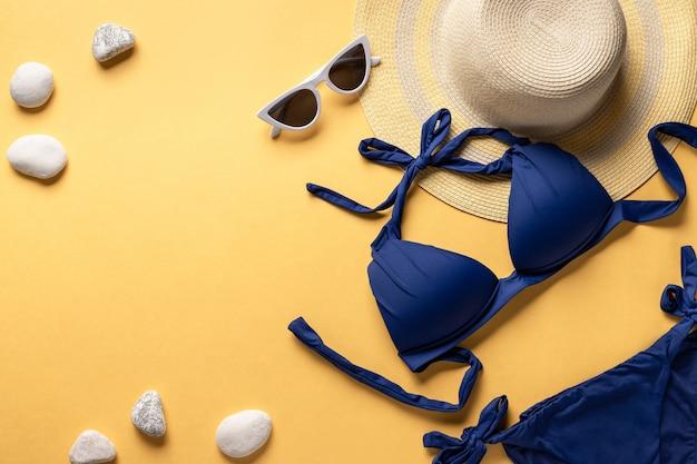 밀 짚 모자, 여자의 비키니 수영복 및 노란색 배경에 태양 안경. 여름 패션 플랫하다. 가로 이미지. 복사 공간.