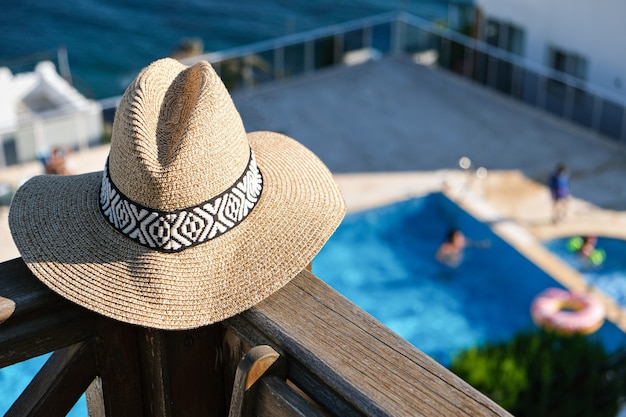 Straw hat on wooden terrace of holiday villa or hotel with chair table with sea and swimming pool view.