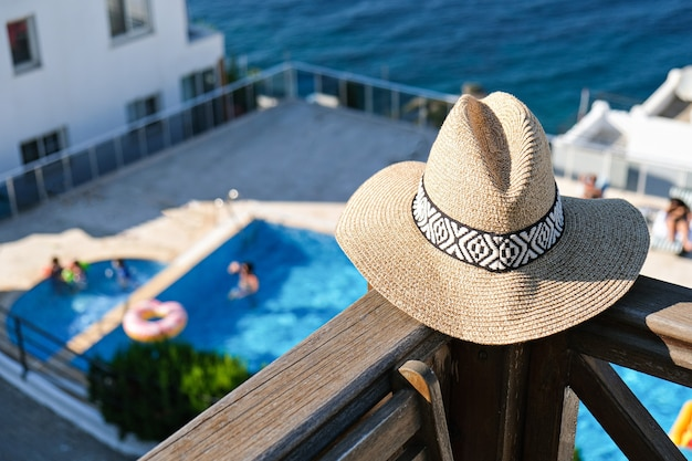 .straw hat on wooden terrace of holiday villa or hotel with chair table with sea and wimming pool view.