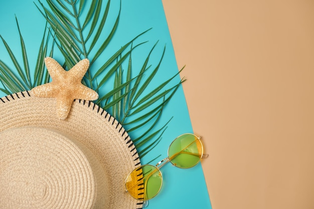 パステルブルーとベージュの表面に麦わら帽子、黄色のサングラス、ヤシの葉、ヒトデ