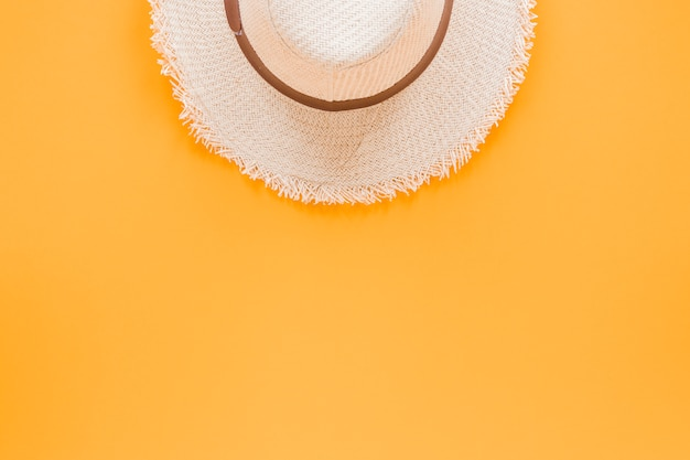 Straw hat on yellow table