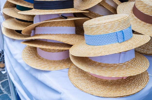 明るい色の女性のための販売のための麦わら帽子。例の展示。