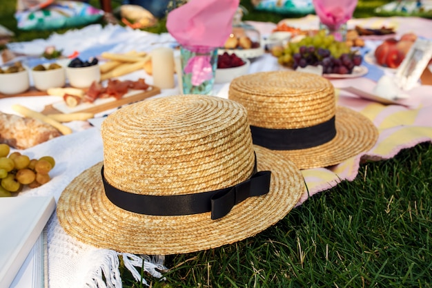 Straw hats lay on a white picnic blanket at green lawn bright summer day