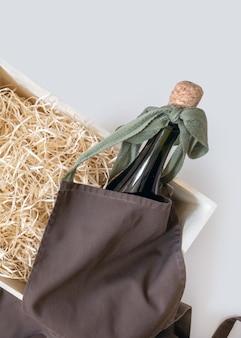収納ボックスにストロー、白い背景にボトルワインと茶色のエプロン、配達サービス。