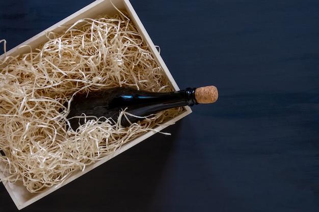 青い木製の背景にワインのボトルが入った収納ボックスにストロー、配達サービス。
