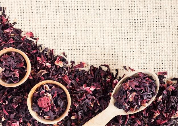 히비스커스 차와 짚 매트 배경 마른 히비스커스 꽃잎이 있는 나무 숟가락