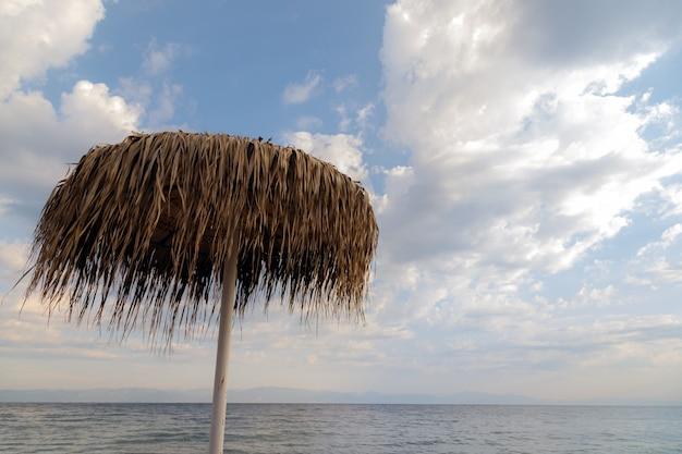 Соломенный зонтик на пляже против облачного неба греция остров тасос летние каникулы