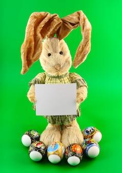 색상 배경에 손에 빈 카드와 함께 밀짚 토끼.