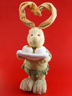 빨간색 배경에 손에 계란과 밀짚 토끼.