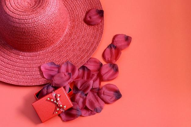 バラの花びらとわらの赤い帽子