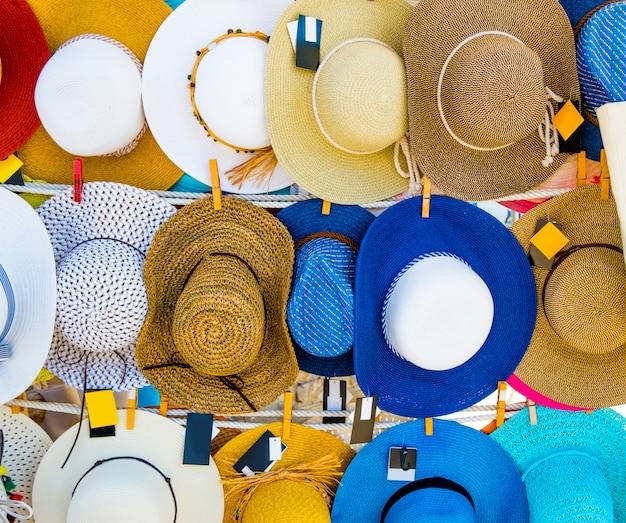 Straw summer hats on market stall outdoor