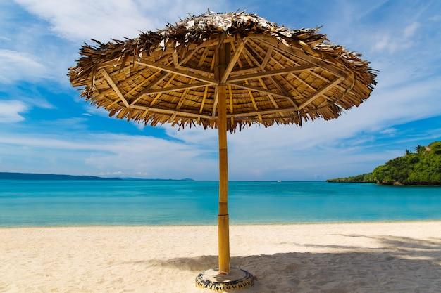 フィリピン、ボラカイ島の熱帯の砂浜にあるわらの傘。夏休みのコンセプト。