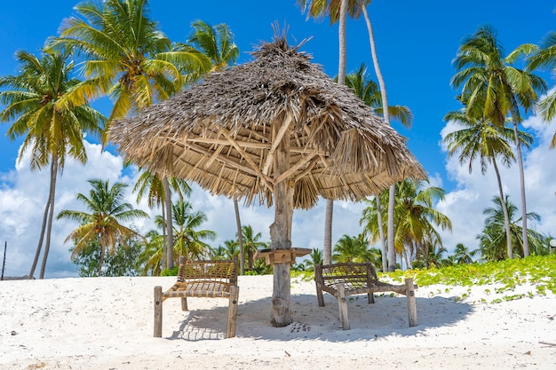 Straw umbrella and two wooden sunbeds on a tropical beach near the sea in sunny day