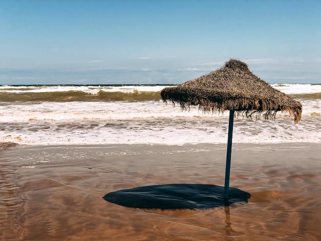 Straw umbrella on wet sandy beach against amazing seascape on sunny day under blue sky