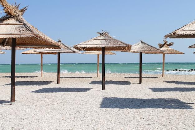 Соломенные зонтики на пустом пляже в летний день