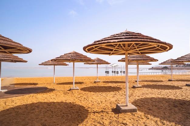 Соломенные зонтики от солнца на песчаном берегу мертвого моря в эйн-бокеке. израиль. красивое место для отдыха и лечения.