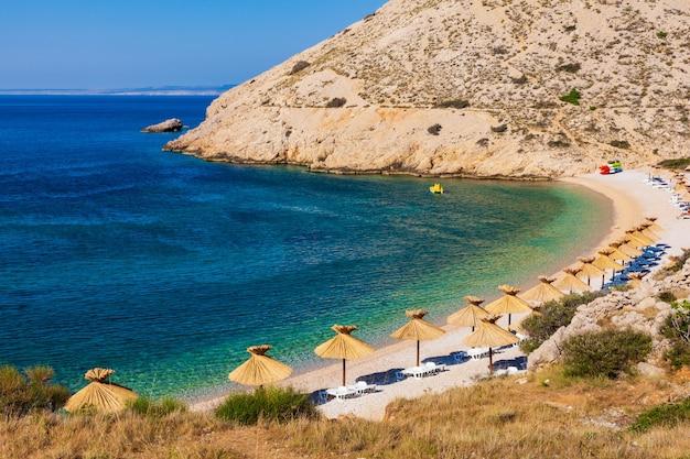 Соломенные зонтики на прекрасном пляже опрна на острове крк, хорватия